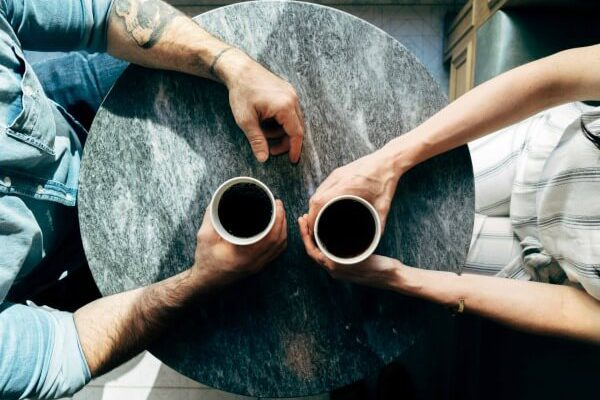 two people's arms holding cups of coffee
