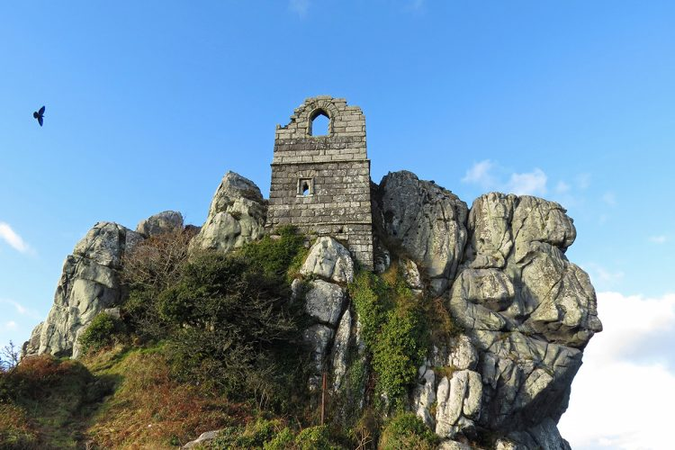 ruined stone tower on clifftop, single bird in blue sky