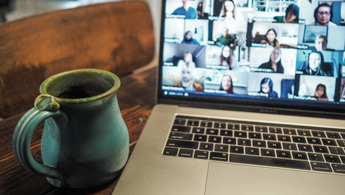 mug on wooden desk beside laptop showing online meeting with 16 people.